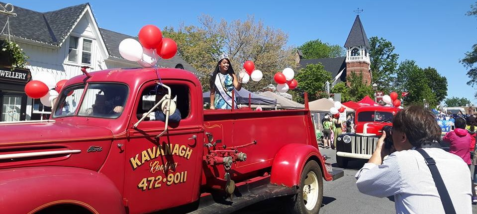 small town parade with beauty queen in old pickup truck