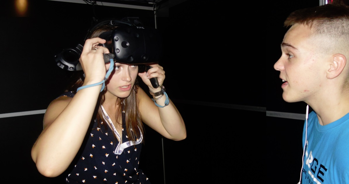 teaching girl how to use VR controllers in the game